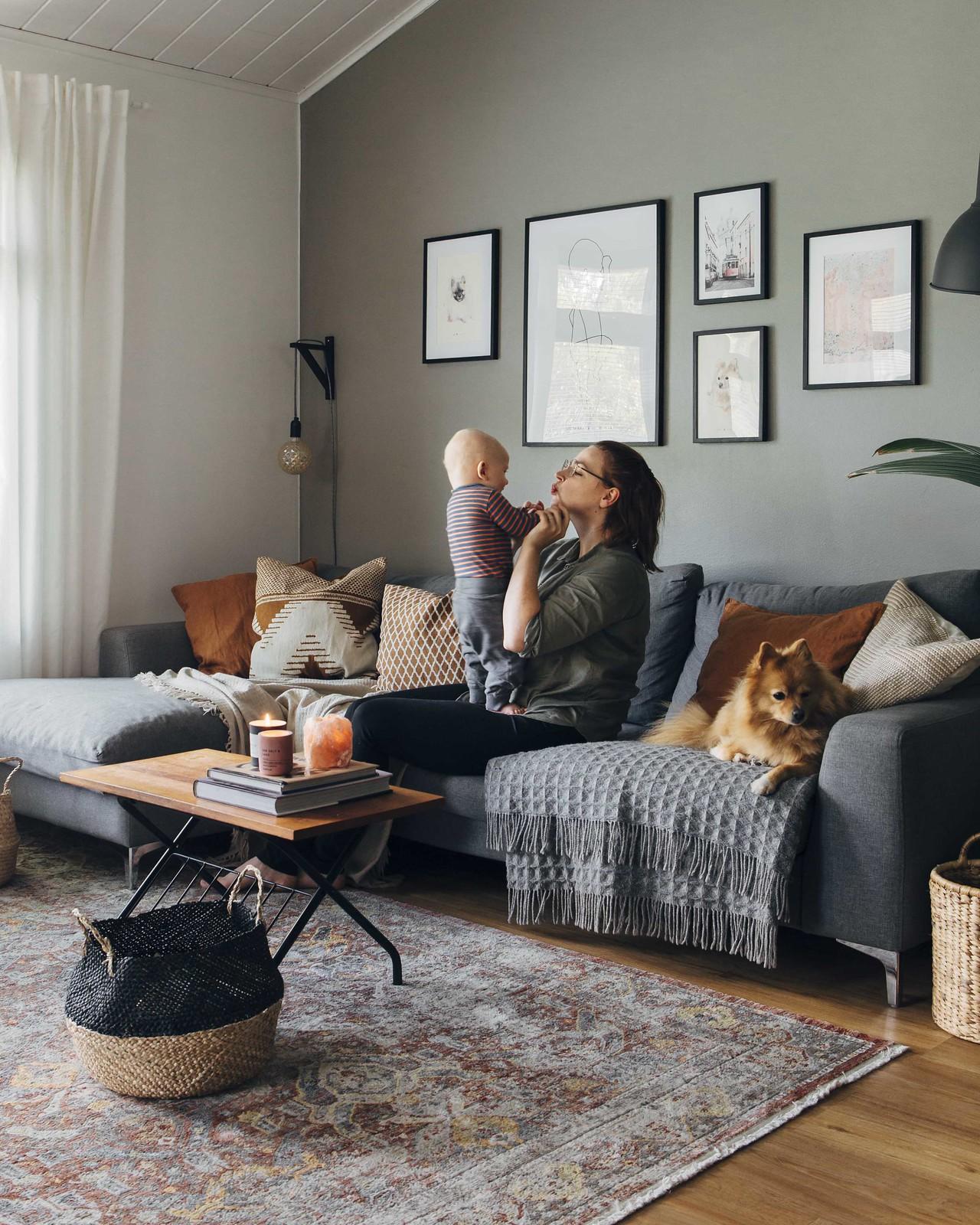 äiti istuu sohvalla lapsi sylissään