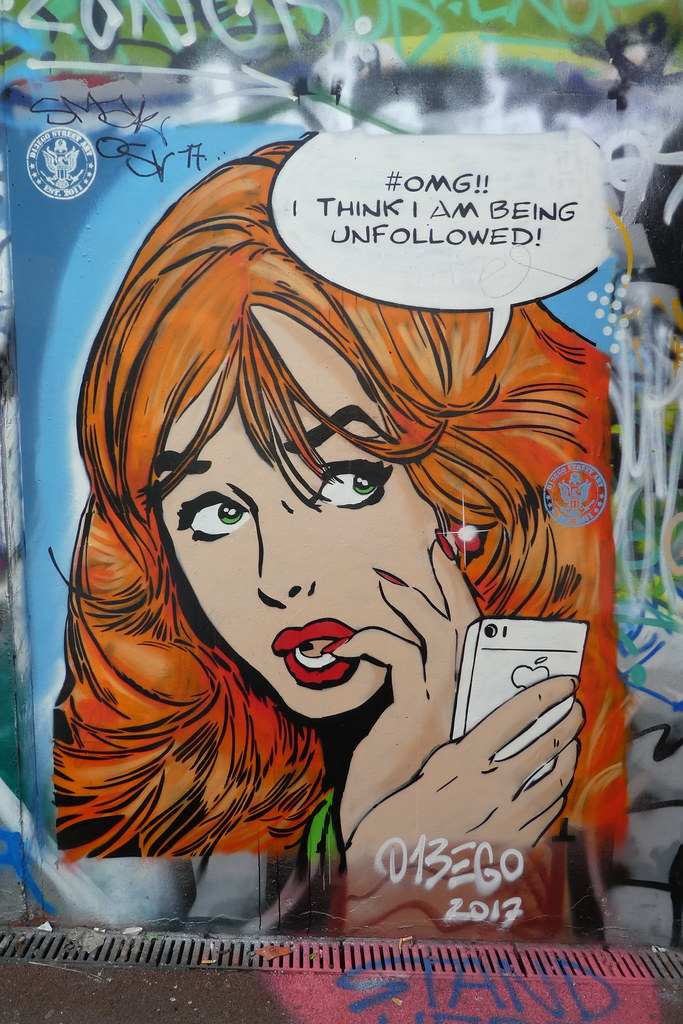 "Figure 3. Photograph of comic-style street art that depicts a close-up woman on her cellphone with a speech bubble that reads ""#OMG I think I am being unfollowed!"""
