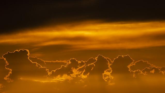 Golden-silhouetted cumulus during sunrise over Guadalajara, Spain.