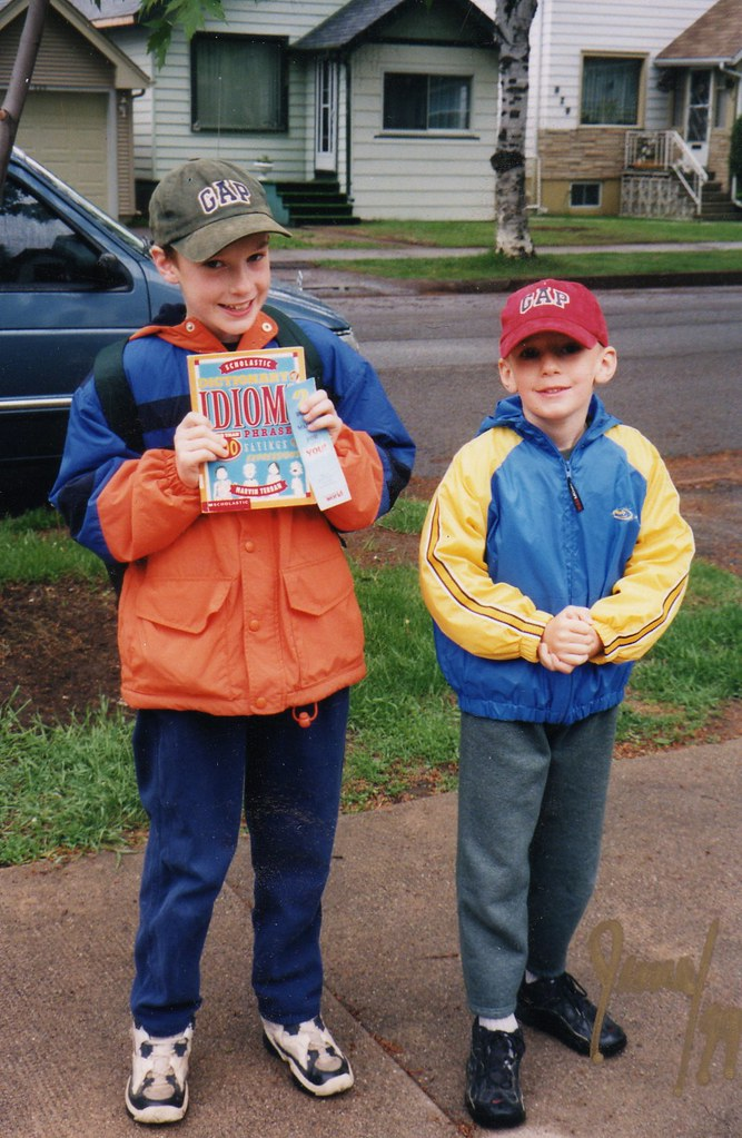 A very young me and my brother, standing next to each other on the sidewalk, in windbreakers.