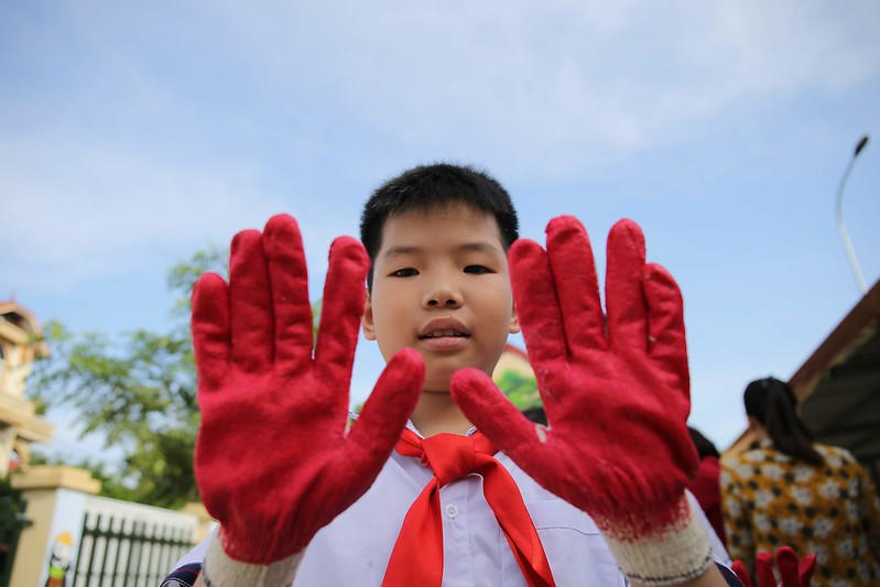 A student wears gloves before planting