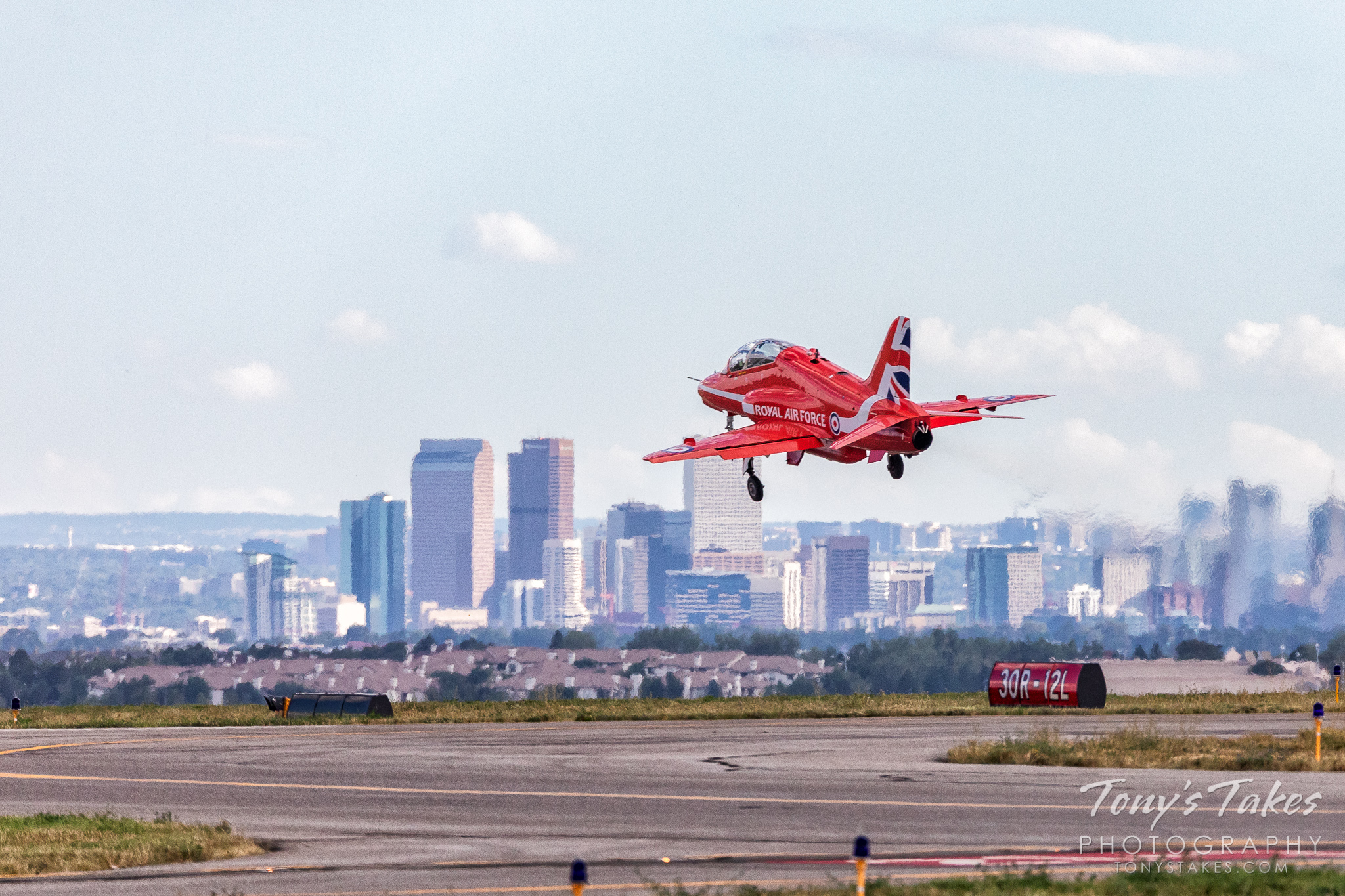 A Royal Air Force Red Arrow jet takes flight with Denver, Colorado in the background. (© Tony's Takes)