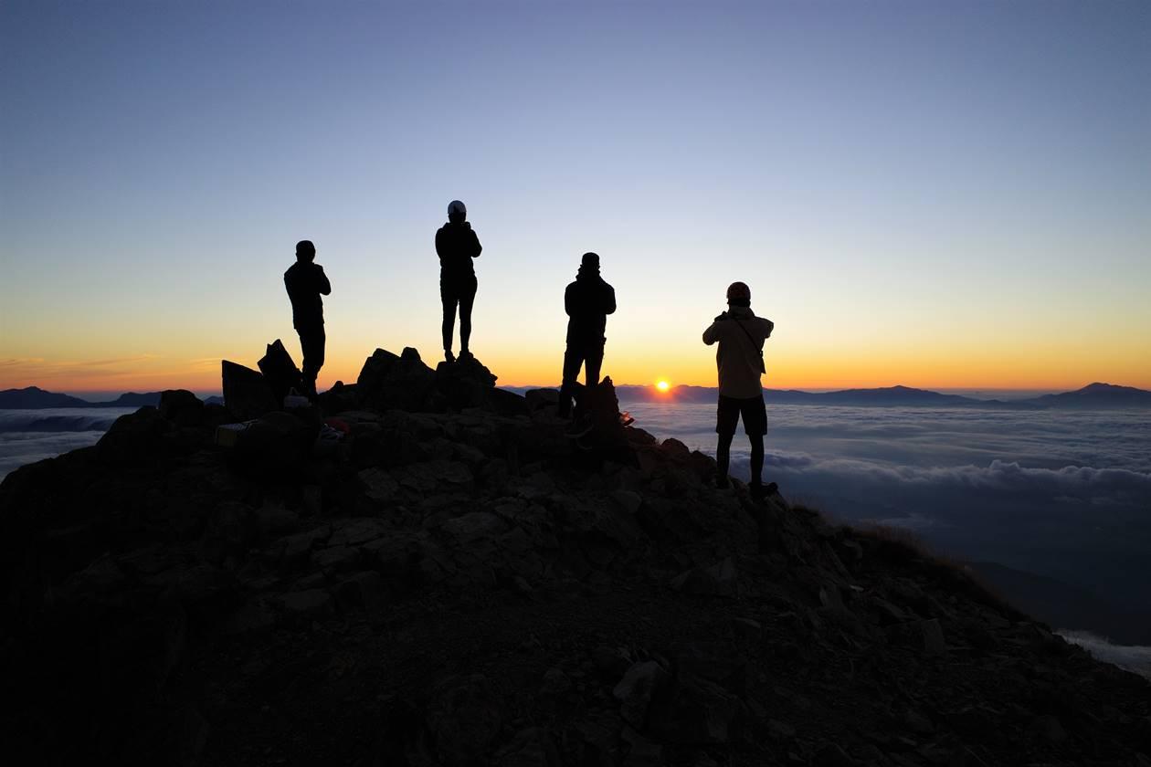 鹿島槍ヶ岳山頂からのご来光と登山者