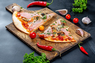 Ham pizza slices on an old wooden kitchen Board with tomatoes, chili and parsley | by wuestenigel