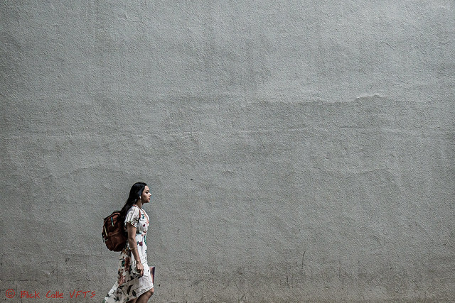 Female Walking in front of Gray Wall