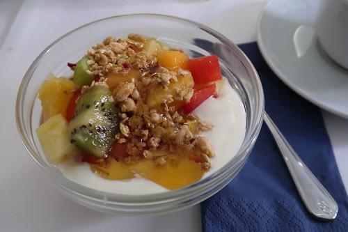 Obstsalat mit Knuspermüsli und Honig auf Naturjoghurt