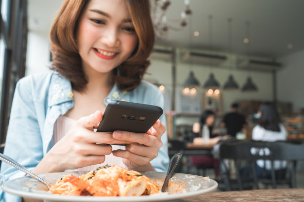 female-blogger-photographing-lunch-restaurant-with-her-phone_7861-1016