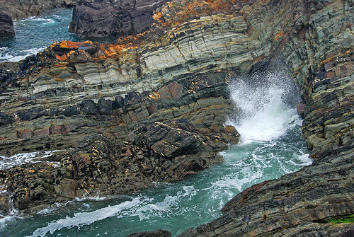 The ocean waves crashing on the striated rocks of the cliffs at Galley Head, Ireland