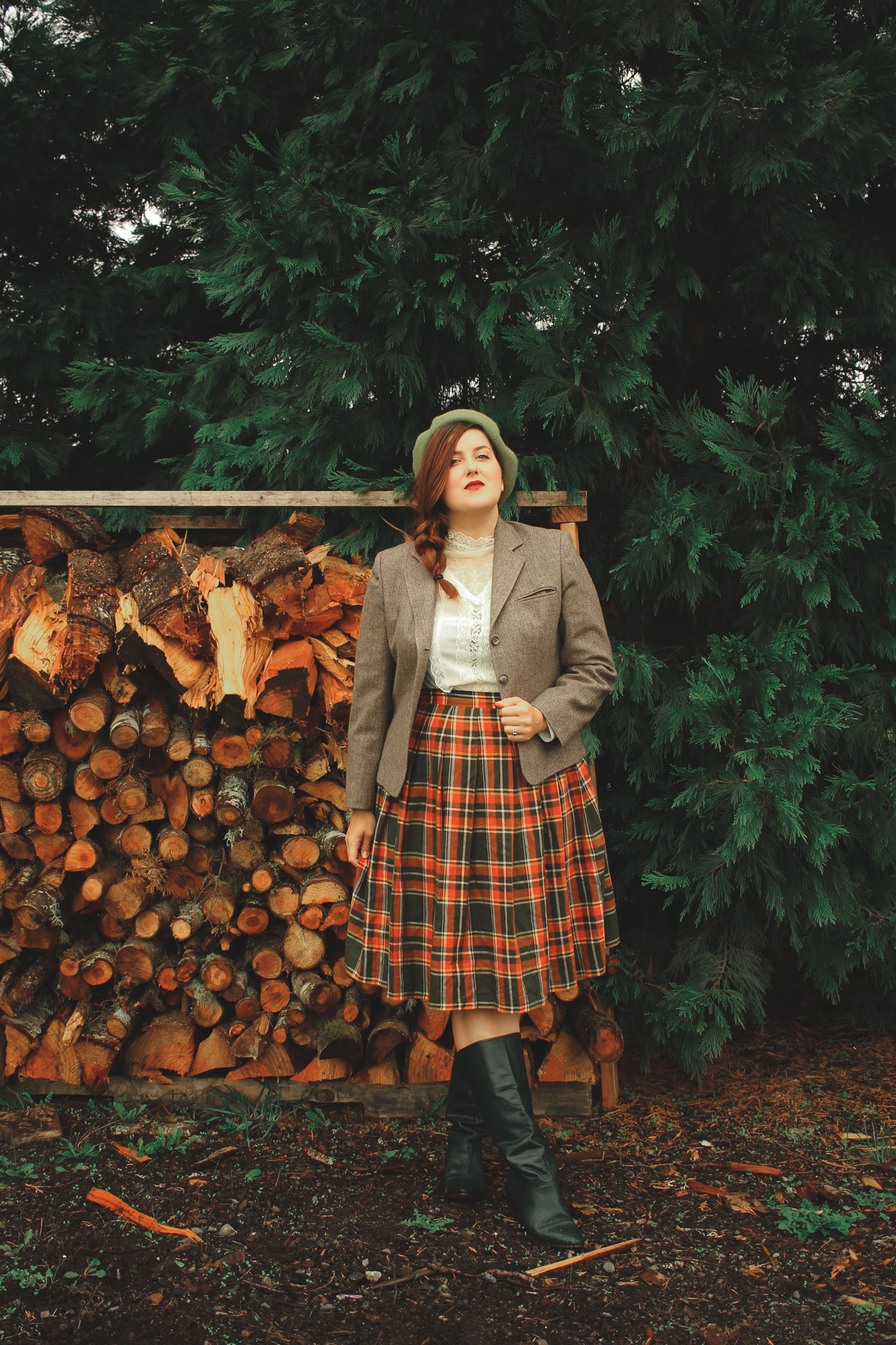 woman wearing a tweed blazer and a plaid skirt in the countryside