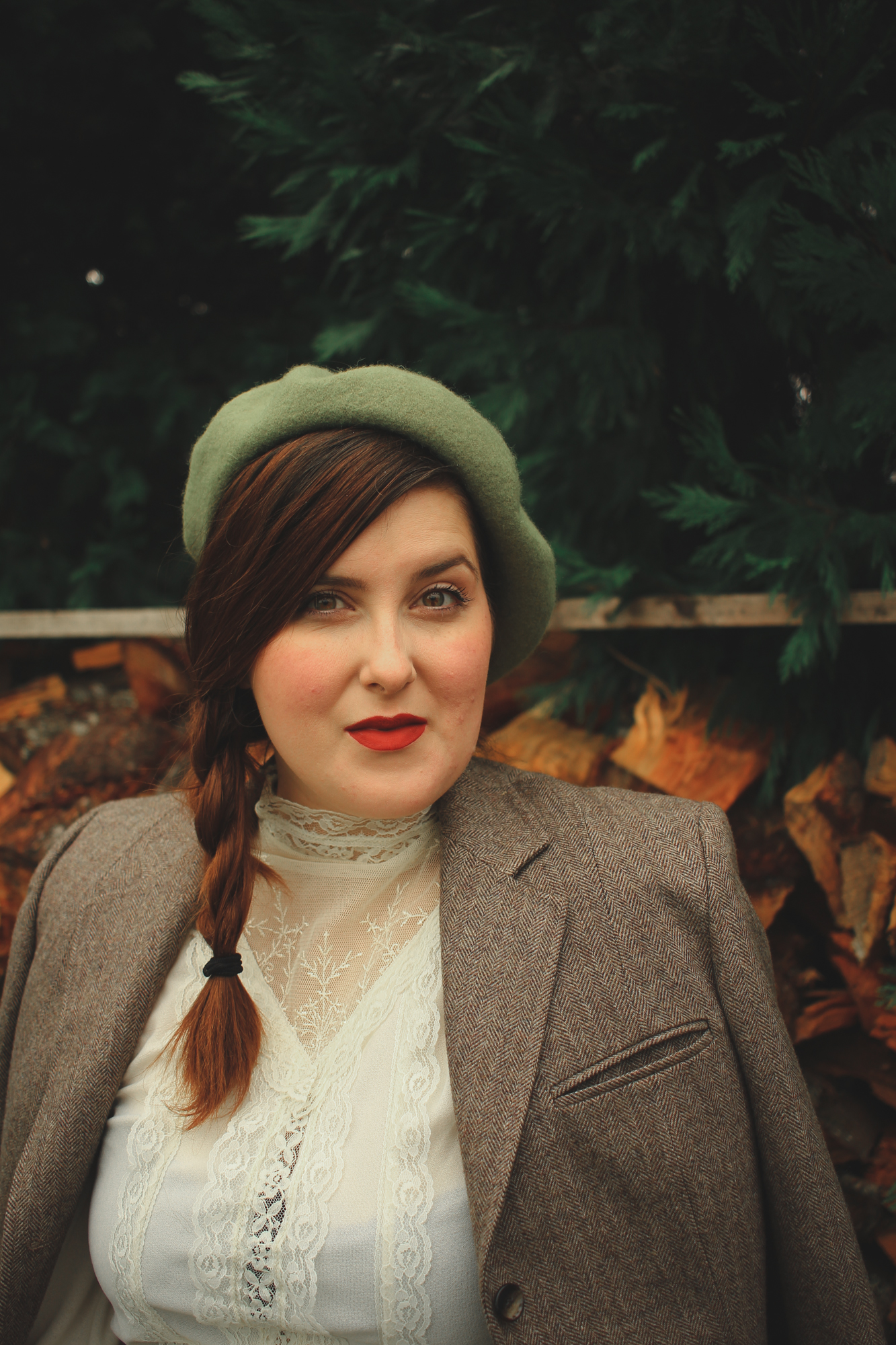 woman wearing a victorian style top and a beret with a blazer