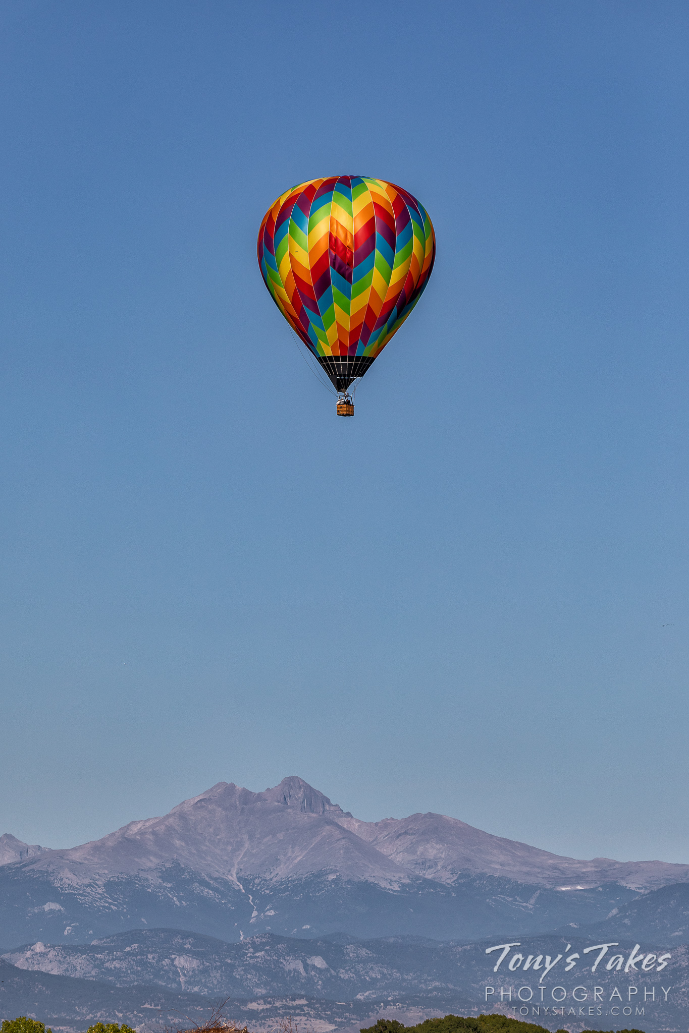 A hot air balloon floats in the air in front of the Rocky Mountains. (© Tony's Takes)