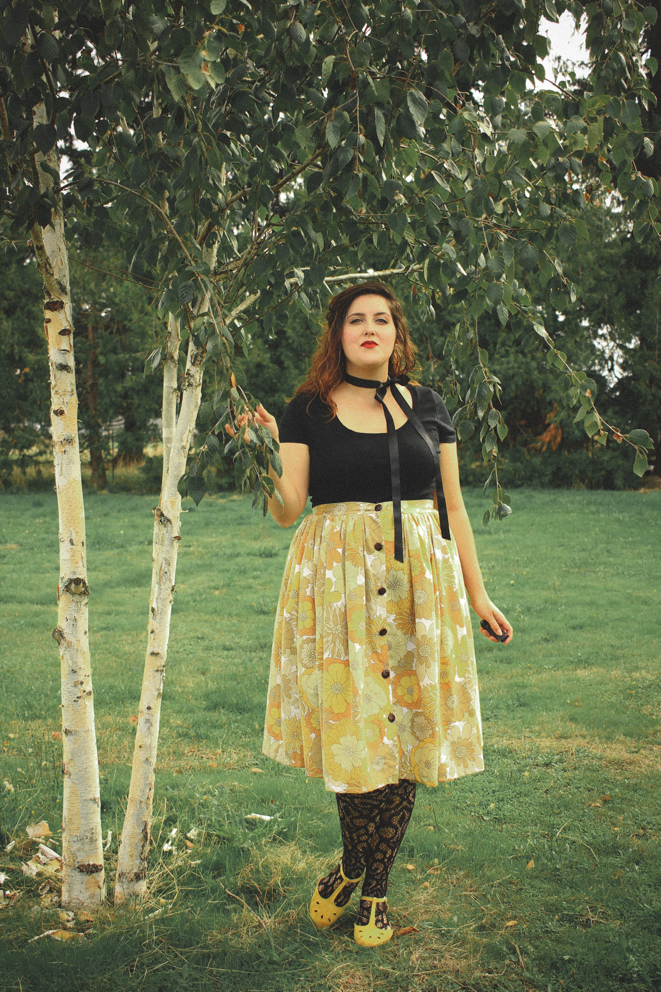 woman wearing a black top, yellow floral skirt, and patterned tights in a retro style
