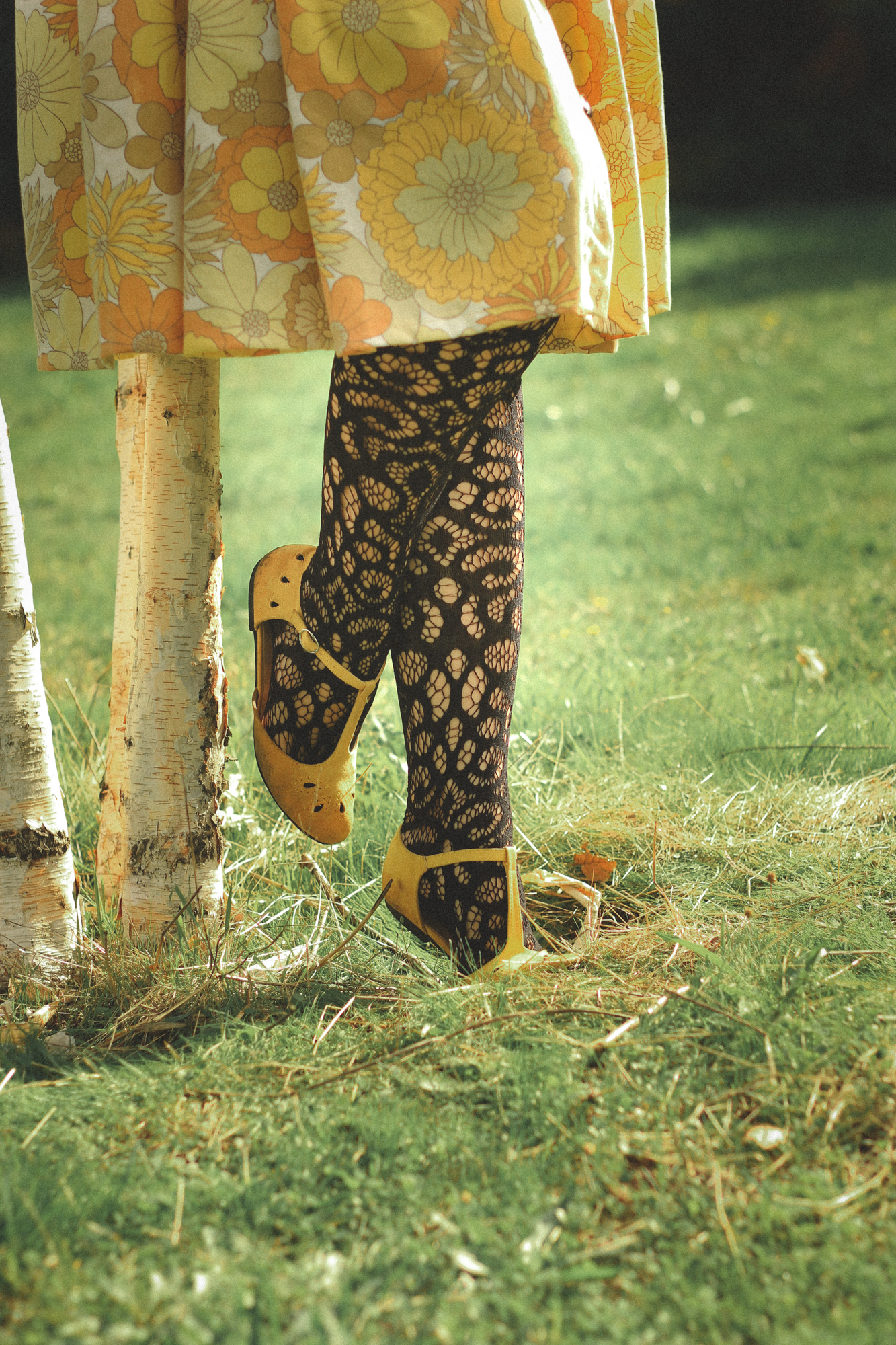 close up of a yellow skirt, black patterned tights, and yellow flats