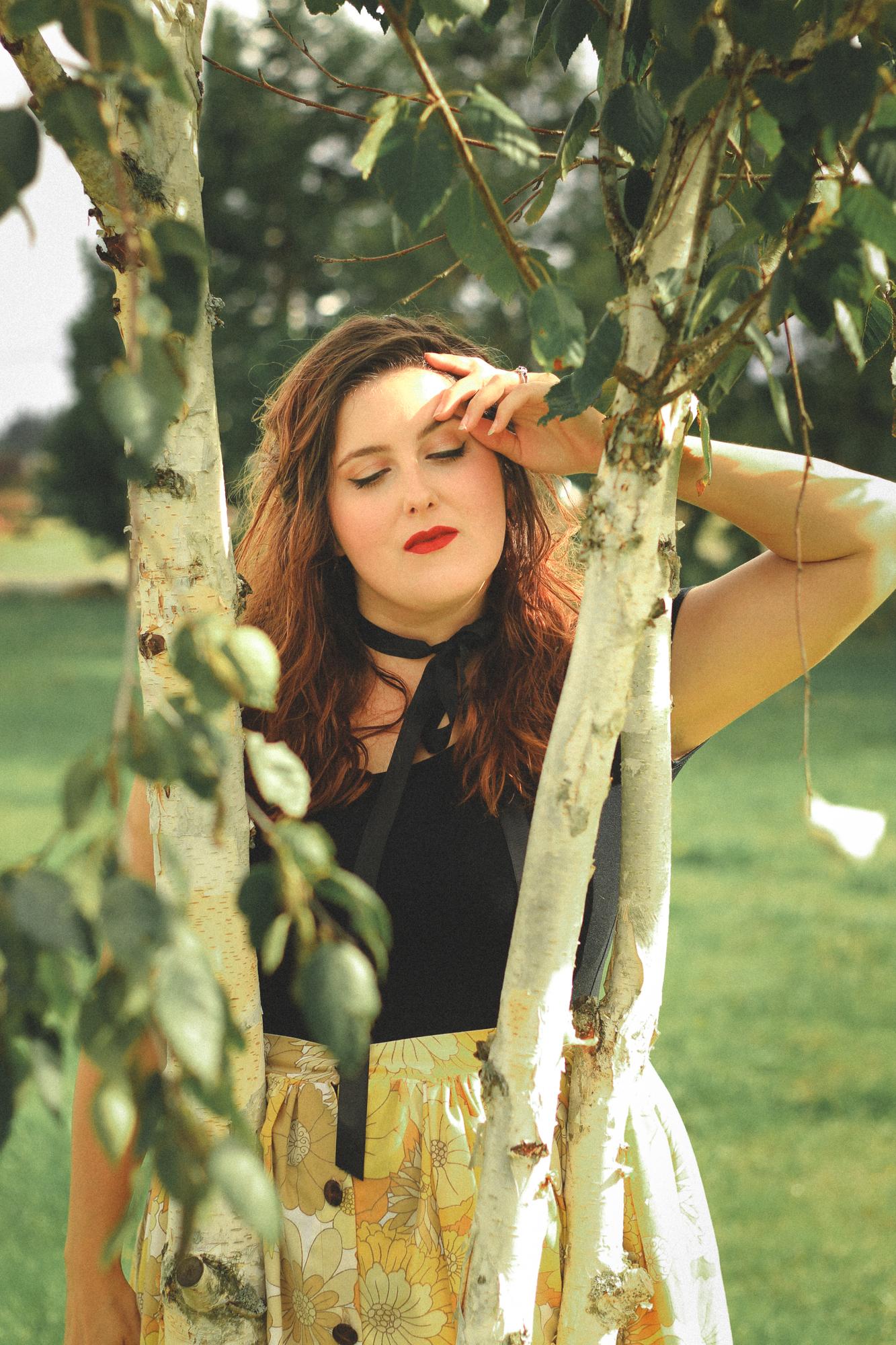 woman posing like a nymph in birch trees