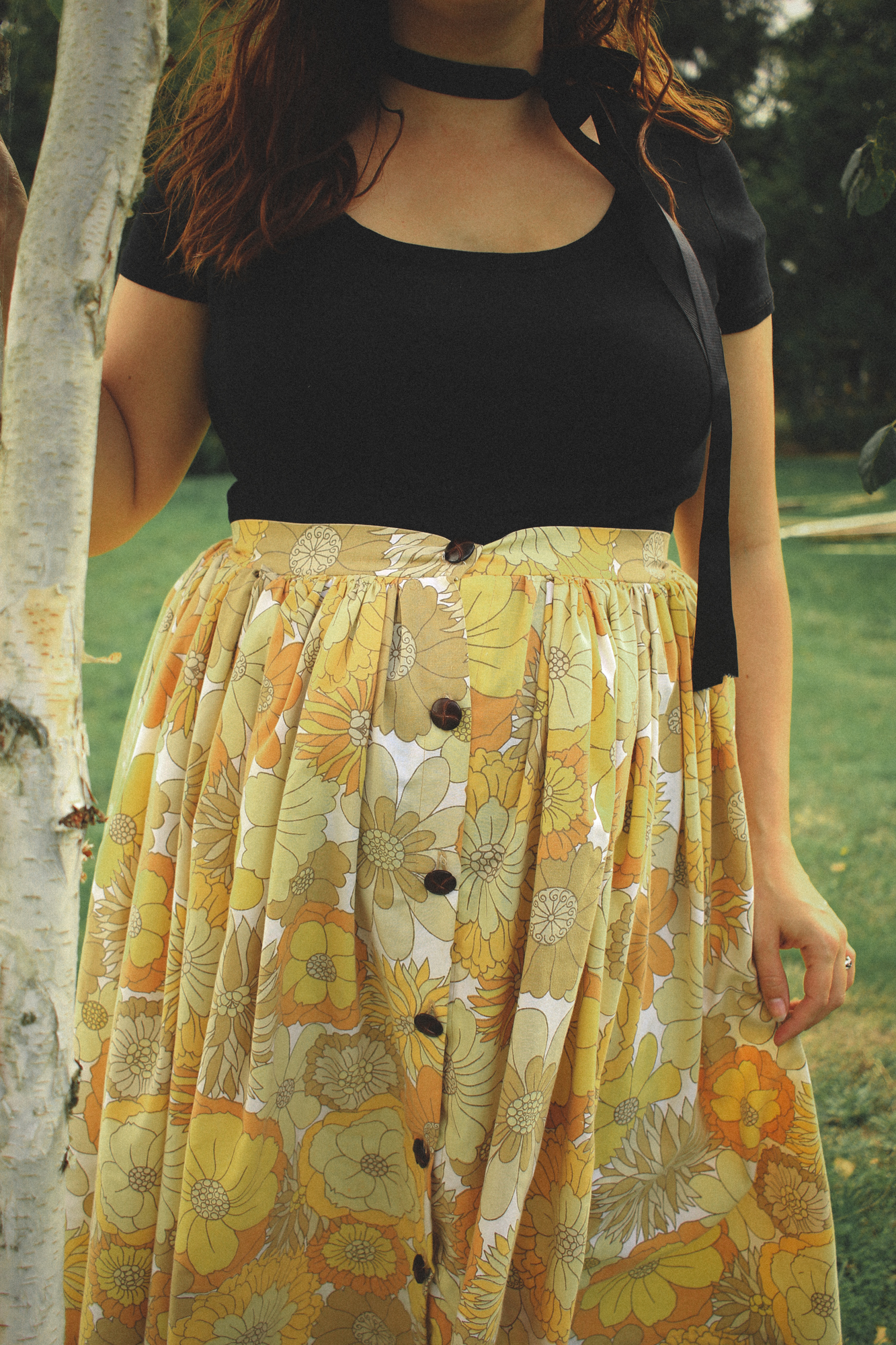 detail of a black top and a floral skirt outfit