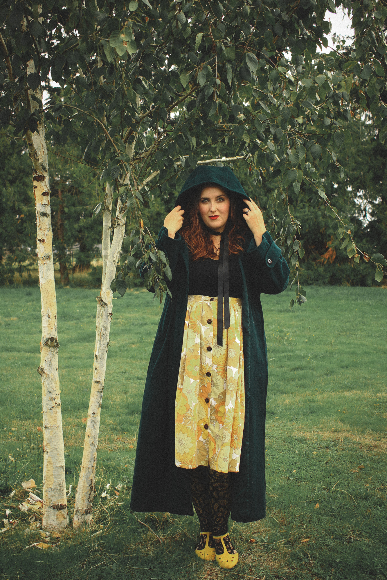 woman wearing a hooded coat and a floral skirt