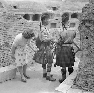An Italian woman inspects the kilts of Pipe Major William MacConnachie and Gordon Highlander Pipe Major  William Boyd at the Colosseum in Rome 6th June 1944.