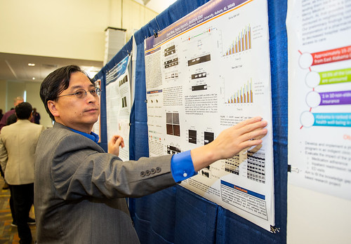 Jianzhong Shen hangs a research poster.