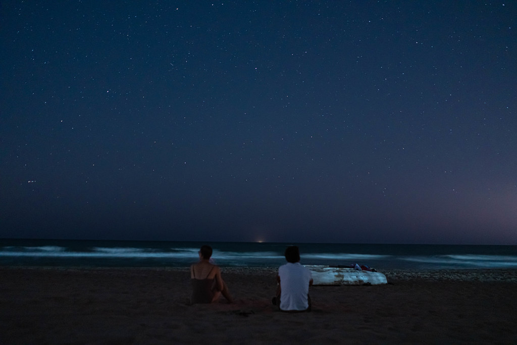Two people on the beach watching stars above the sea | Flickr
