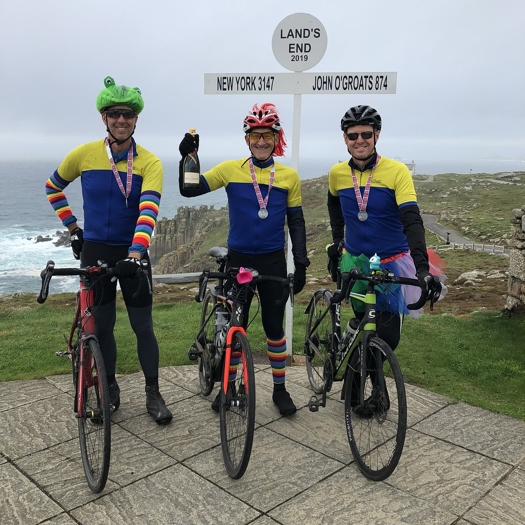 Three happy cyclists at the Land's End sign post