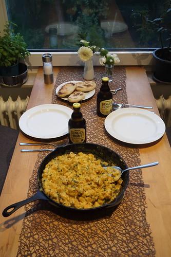 Indisch anmutendes Kürbisgericht mit in der Pfanne gebratenem Hefefladenbrot (Tischbild)