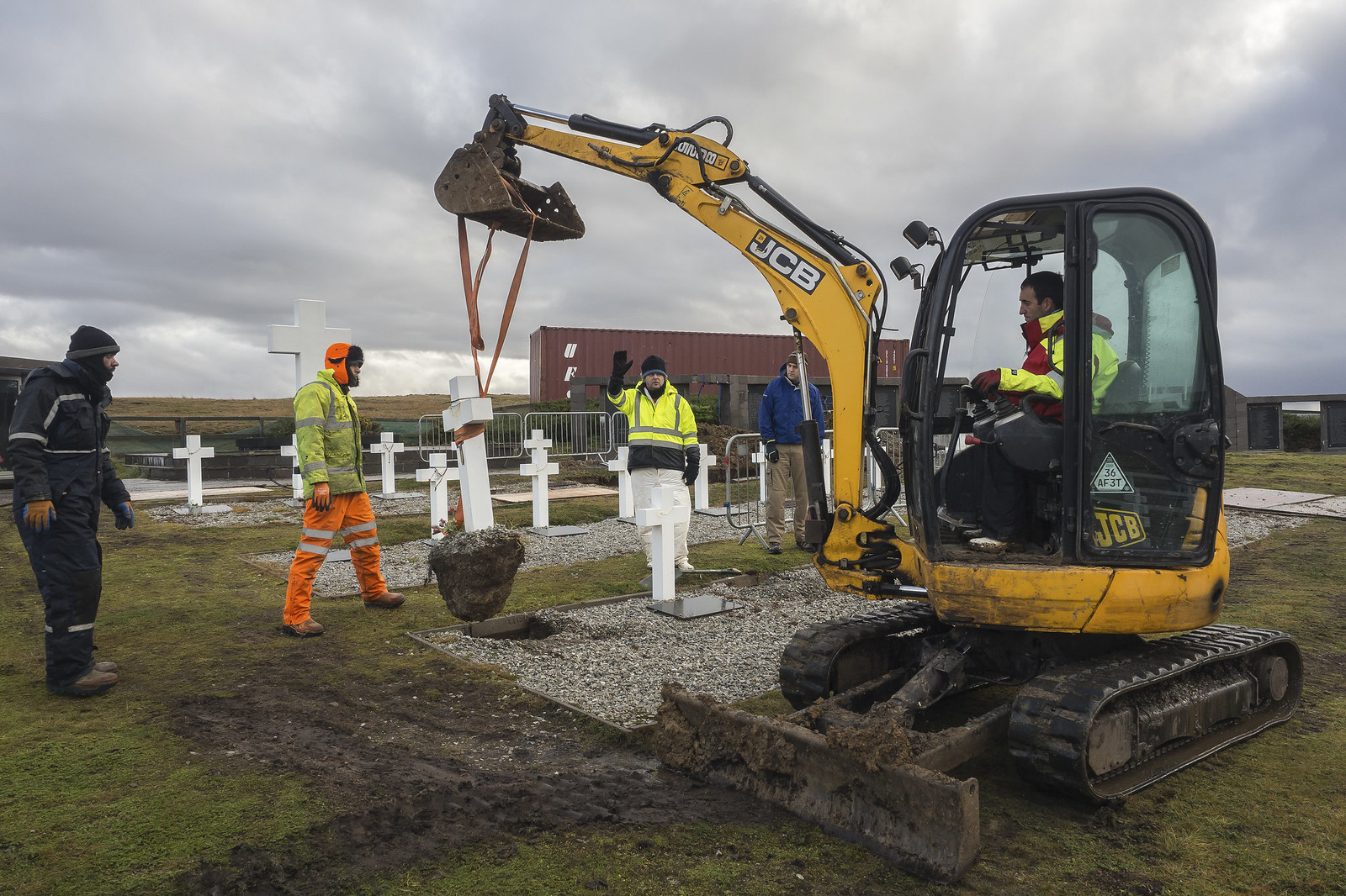 A mechanical digger clearing grave sites in a cemetery in order to identify the deceased to confirm identity