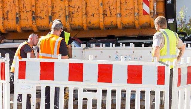 Vier Straßenbauarbeiter auf einer Baustelle