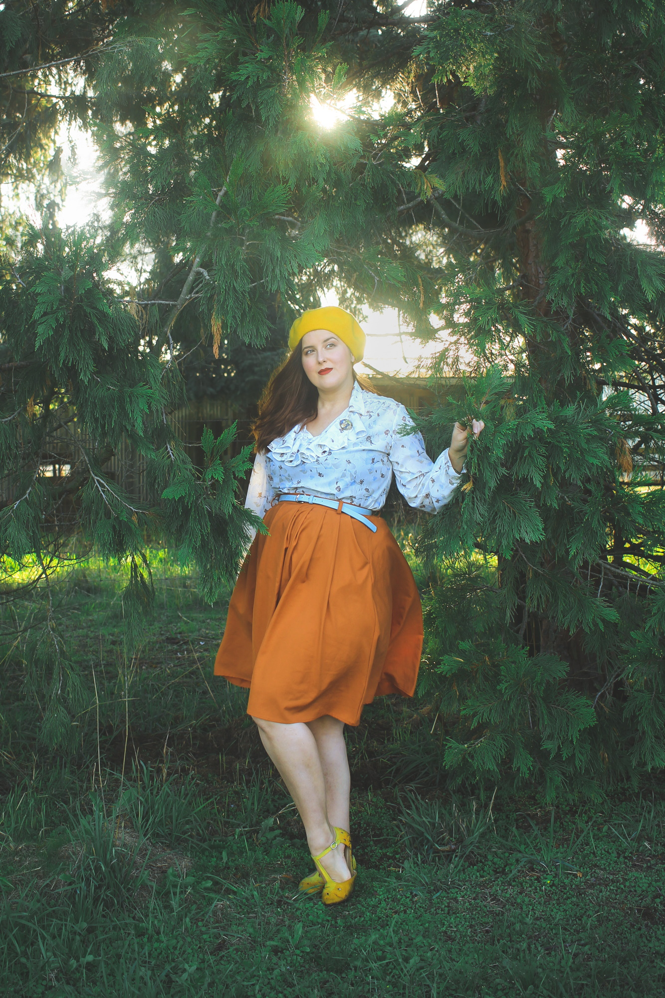 woman wearing a ruffled blouse and orange skirt and yellow beret