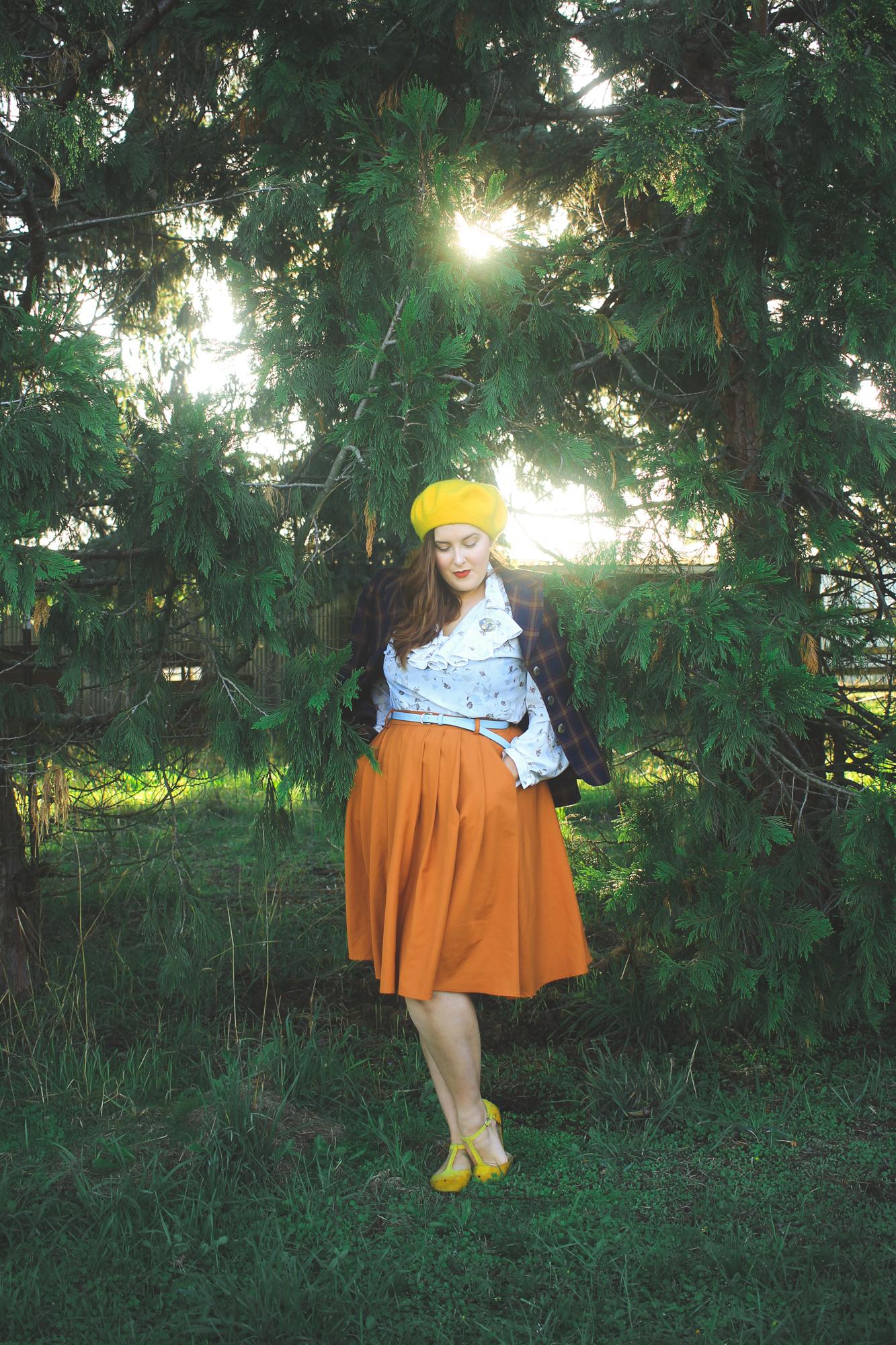 woman wearing a plaid blazer, ruffled blouse, and orange skirt