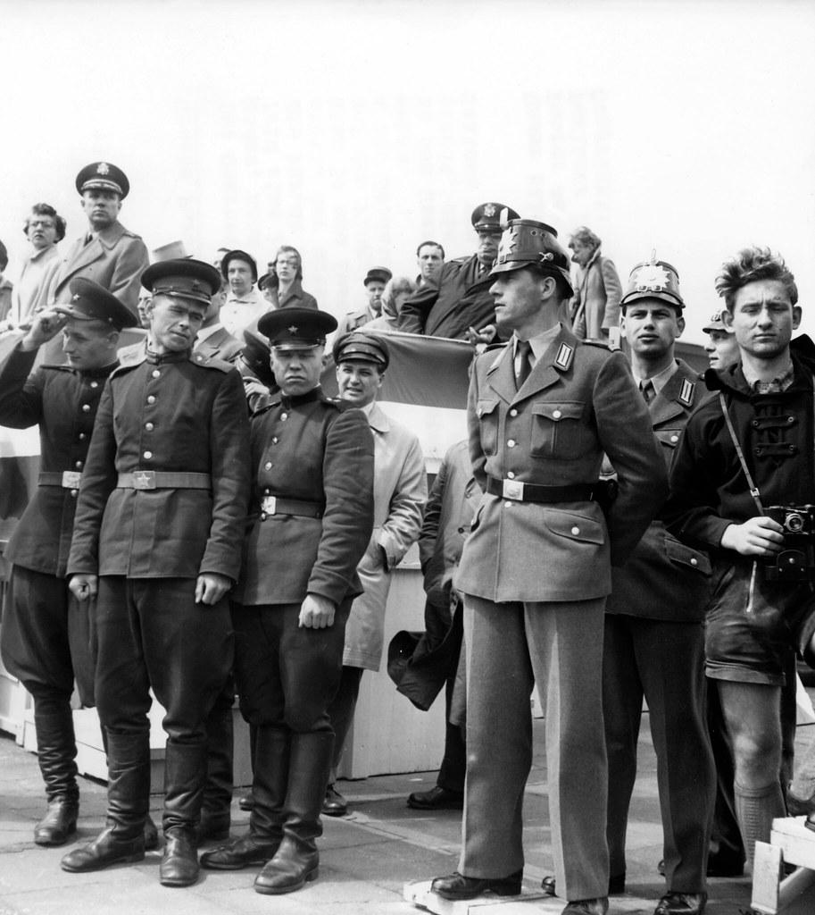 1958. Советские солдаты и полицейские из полиции Западного Берлина наблюдают за военным парадом по случаю «Дня вооруженных сил» в аэропорту Темпельхоф в Берлине 17 мая