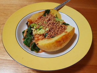 Baked potato with baked beans, spinach, avocado, and bacon bits
