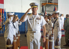 Rear Adm. George M. Wikoff commander of Task Force 70, salutes sideboys as he departs a change of command ceremony in the USS Ronald Reagan (CVN 76) hangar bay, Sept. 29. (U.S. Navy/MC1 Alexandra Seeley)