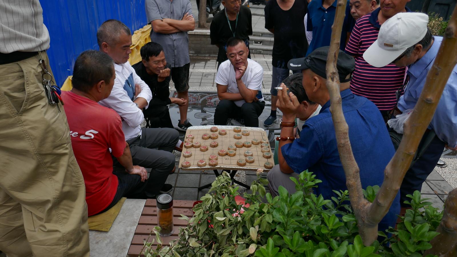 Una de las muchas mesas jugando a Xiangqi en la calle
