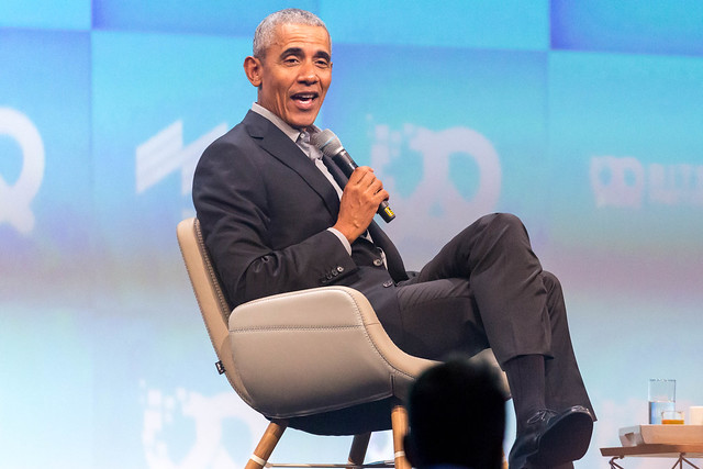 Former Potus Barack Obama sits on a chair and holds a microphone while talking at Bits & Pretzels investors festival, around Oktoberfest in Germany