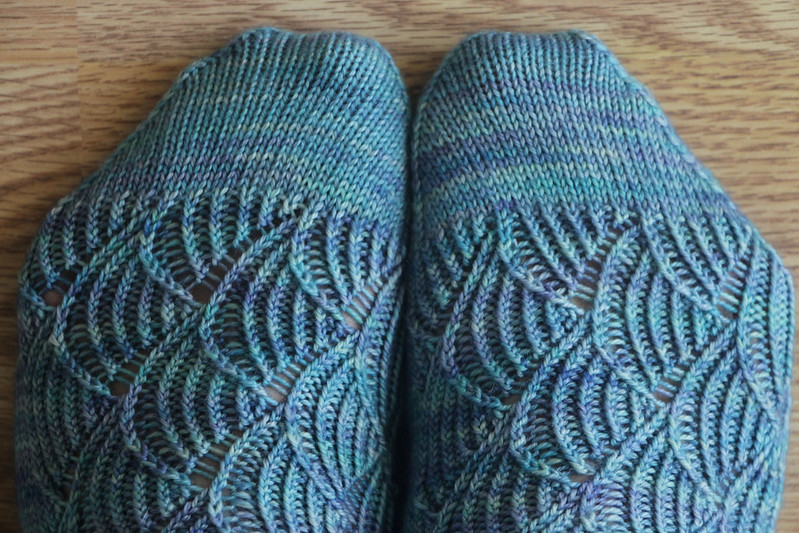 Detail view of handknit Pomatomus socks, showing toes with coordinating yarn striped in