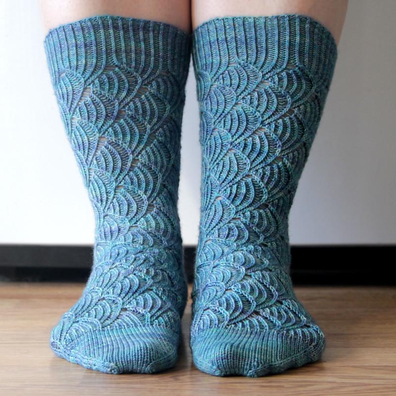 Handknit Pomatomus socks, modeled on parallel feet facing forward