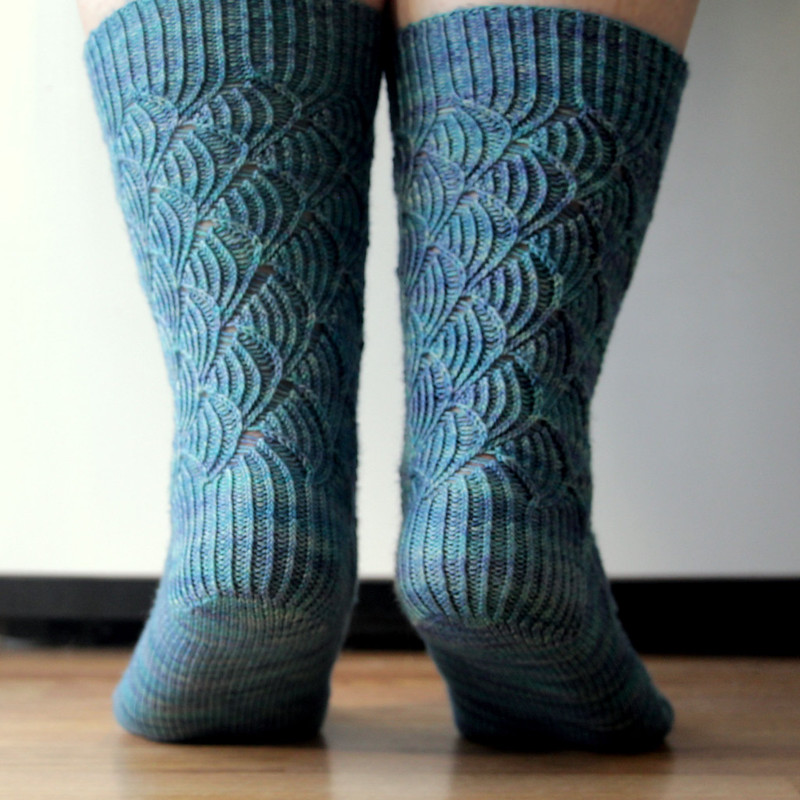 Handknit Pomatomus socks modeled on feet, standing slightly on tip-toe and viewed from behind to show heel detail