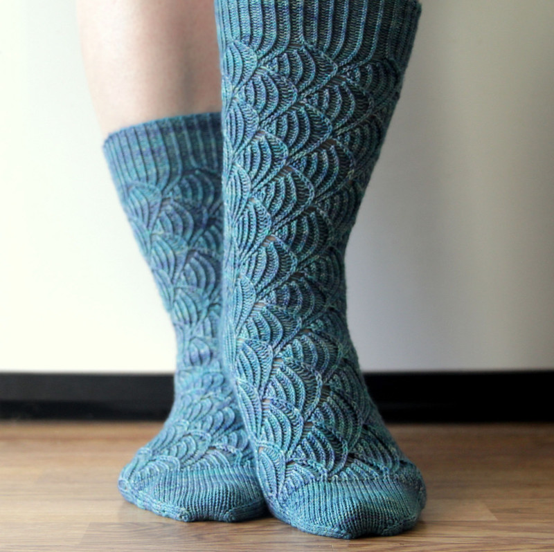 Handknit Pomatomus socks, modeled on feet, with one stepping in front of the other