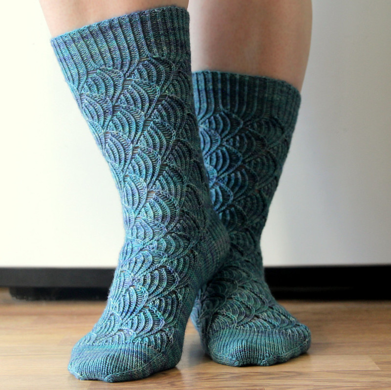 Handknit socks from the Pomatomus pattern by Cookie A, in variegated blue yarn, modeled on feet