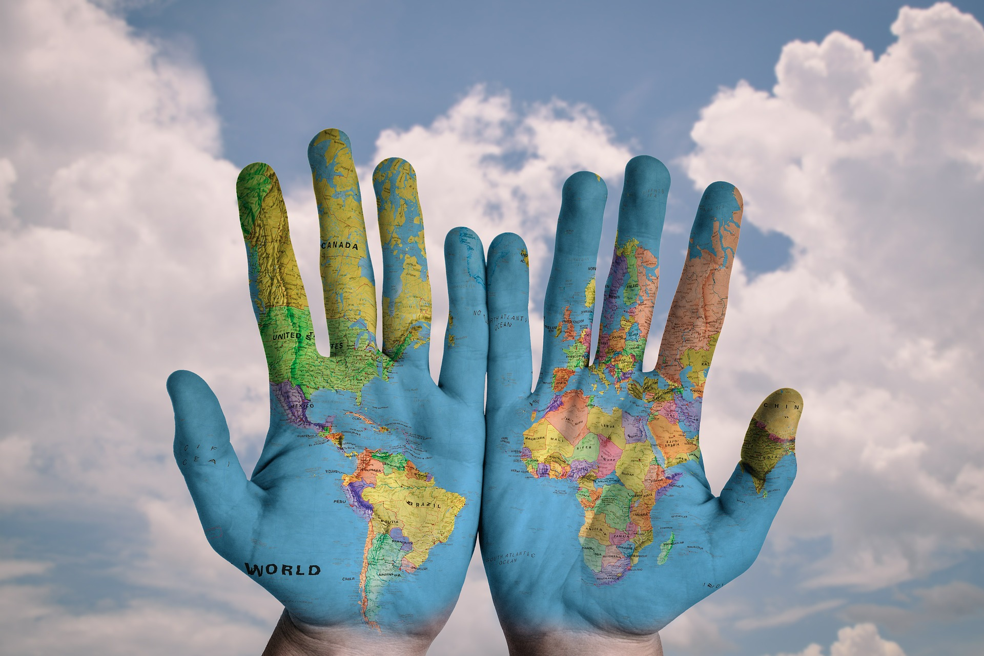 A pair of hands with a multi-coloured map on the palms and the sea set against the sky which is cloudy.