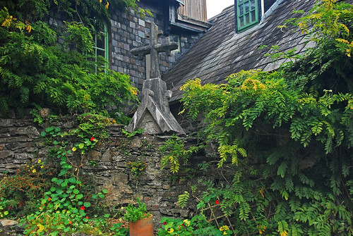 A slate roof top overgrown with green vines and a stone cross in Kinsale, Ireland