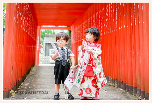 双子の兄弟の七五三 神社の赤い鳥居の下で記念撮影 千歳飴を持って