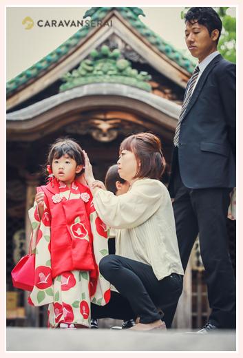 3歳の女の子の七五三 神社の境内でヘアスタイルを直すママ