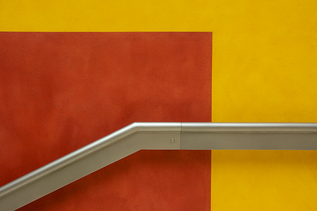 Handrail on a yellow and red wall
