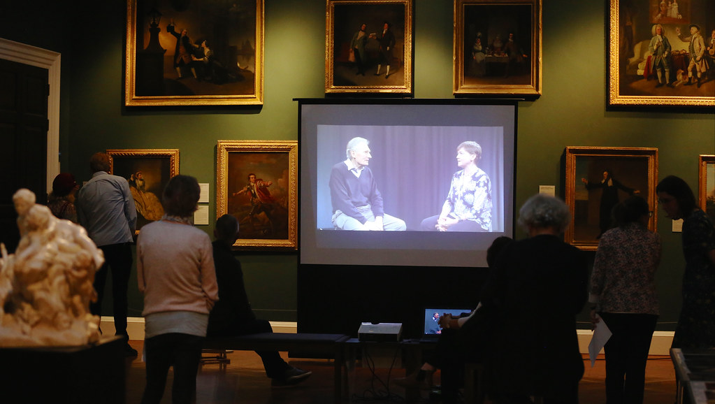 People seated around a large projection of a film in a museum gallery