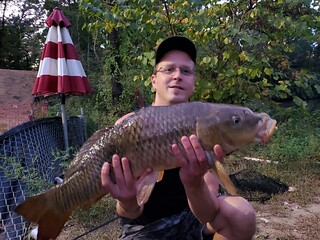 Photo of man with a big carp he caught in the Patapsco River.
