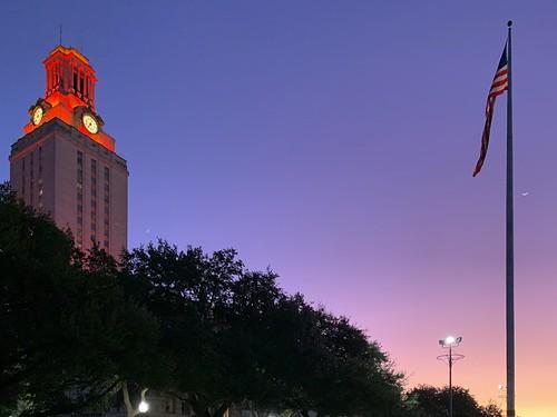 Burnt-orange-lit UT Tower, US flag and crescent moon