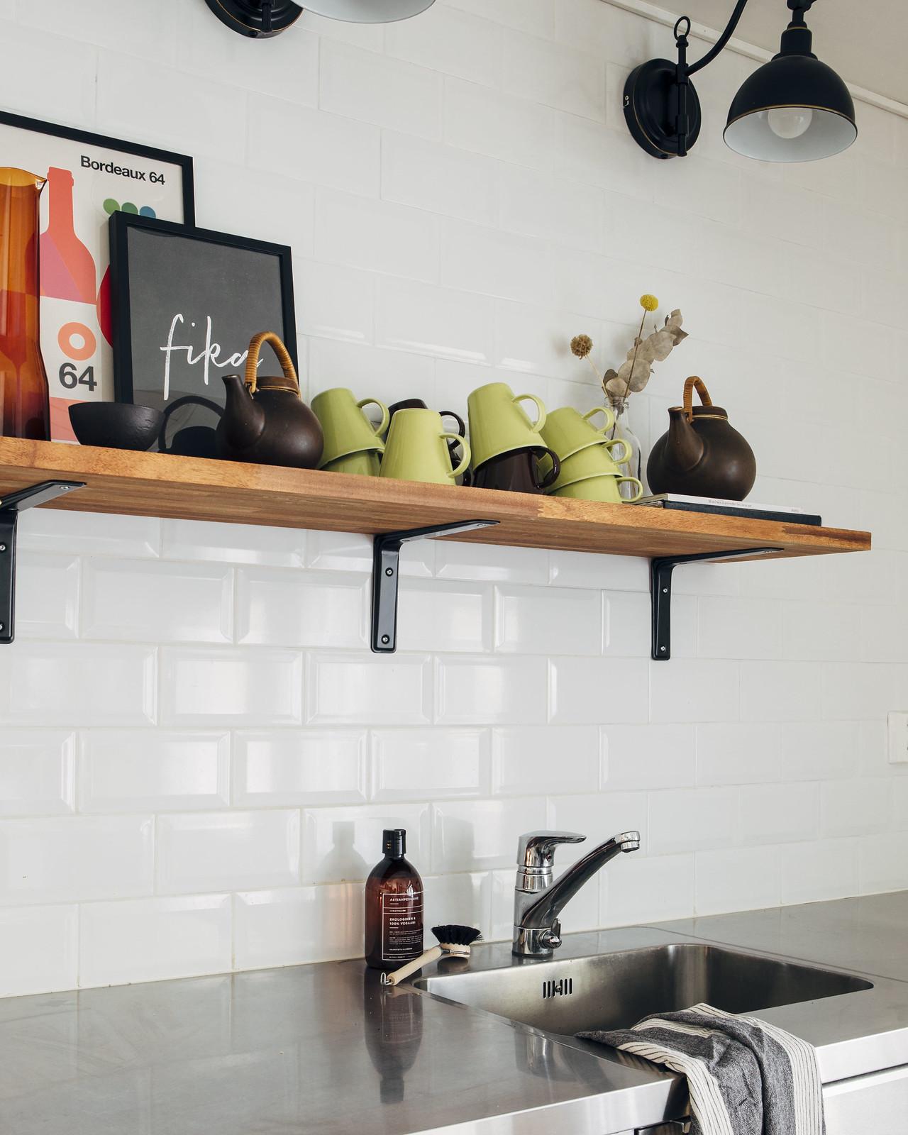 Puinen avohylly keittiössä. Hyllyn päällä on kahvimukeja, tauluja ja vintagekeramiikkaa