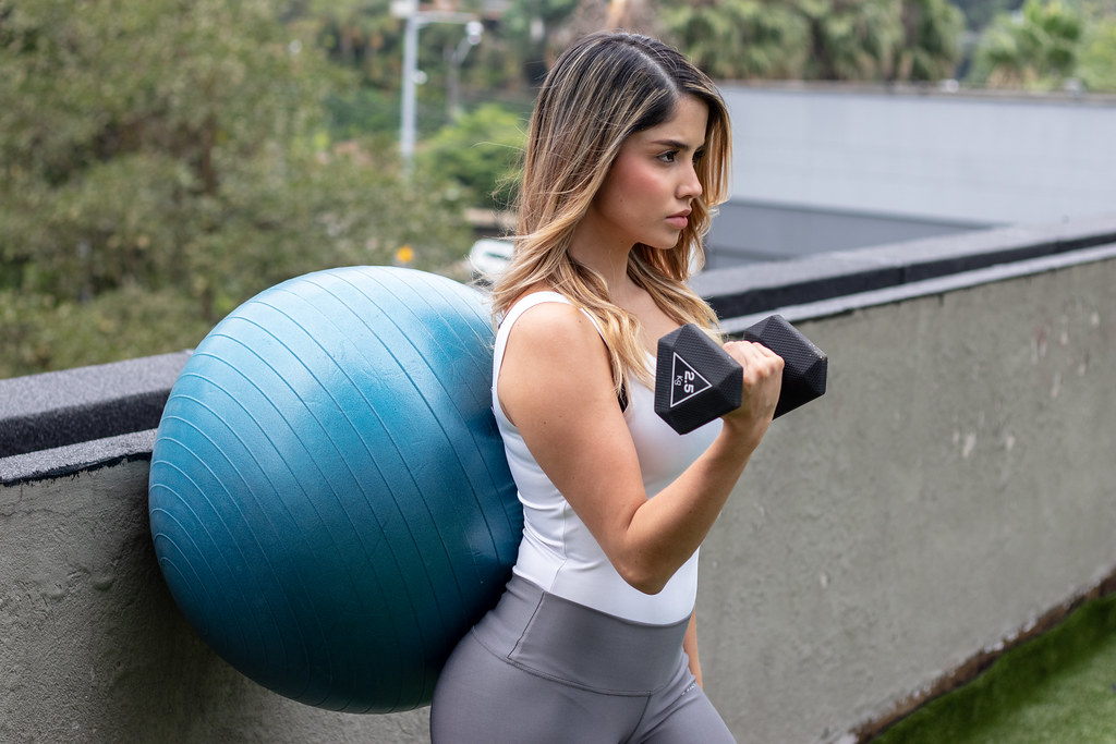 Girl doing one arm dumbbell curl exercise