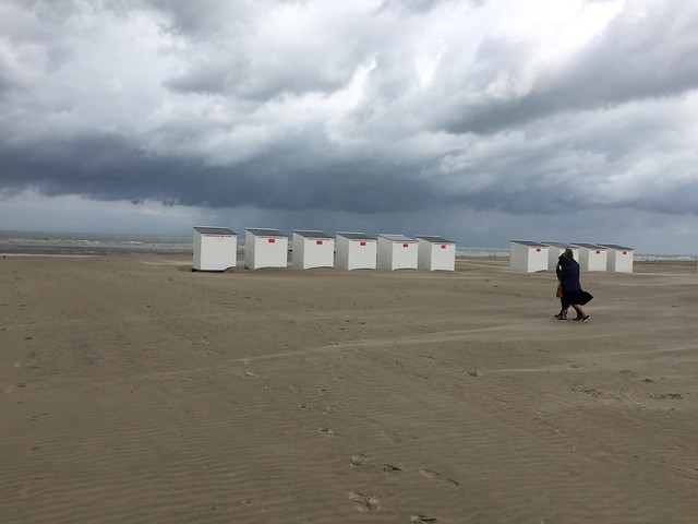 Beach changing huts with a nice cloud cover & very windy over the North see beach where shrimp fishing with Belgian horses tradition since the 1500 , Martins photograph , Oostduinkerke , now Koksijde , West Vlaanderen , West Flanders , Belgium June 8 2019